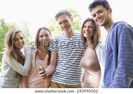 Happy students looking at smartphone outside on campus at the university - stock photo