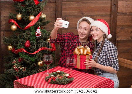 Happy students making selfies during New Year and Christmas holidays in the restaurant. People smiling: girl holding a box of present, man photographing. - stock photo