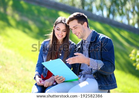 Happy students sitting in park - stock photo
