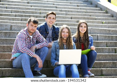 Happy students sitting on stairs in park - stock photo