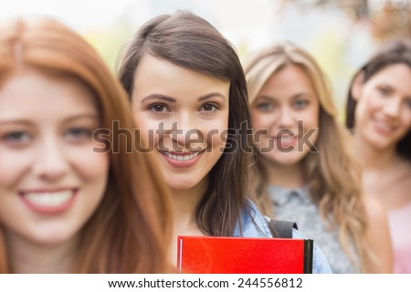 Happy students smiling at camera in a row at the university - stock photo