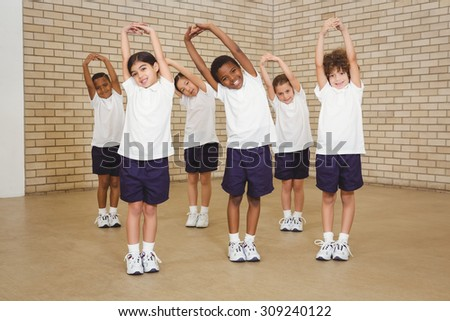 Happy students stretching out together at the elementary school - stock photo