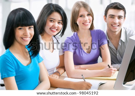 Happy students studying together with computer