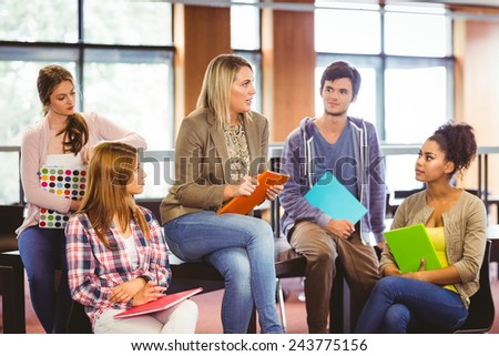 Happy students talking with their teacher in the library - stock photo