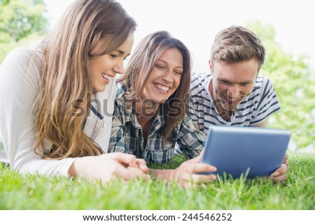 Happy students using tablet pc outside at the university - stock photo