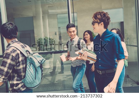 Happy students walking out of the school building - stock photo