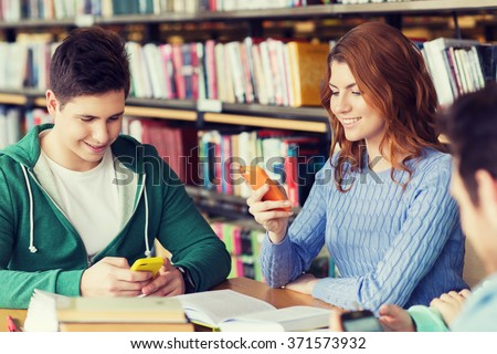happy students with smartphones texting in library