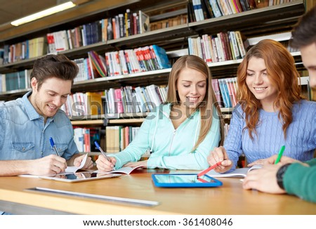 happy students with tablet pc in library