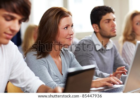 Happy students with their laptops in university class - stock photo