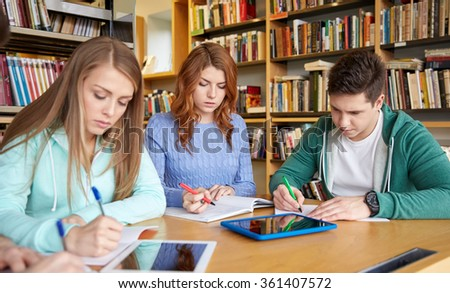 happy students writing to notebooks in library - stock photo