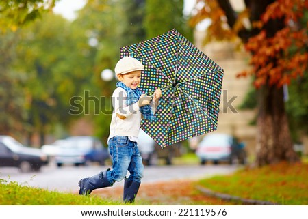 happy stylish boy with umbrella running in park