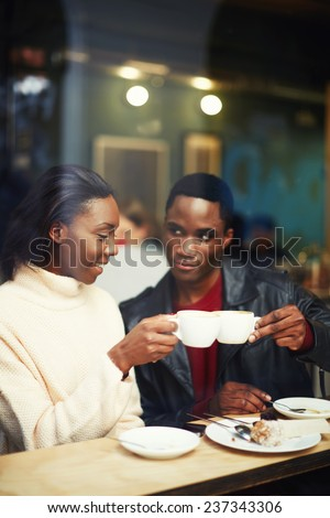 Happy stylish friends having coffee together, laughing young couple in cafe, having a great time together,view through cafe window, beautiful couple clinking cups while smiling  sitting in coffee shop - stock photo