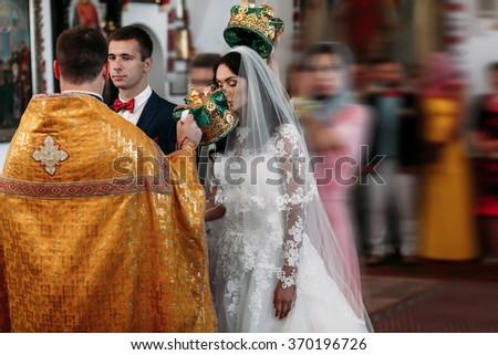 Happy stylish newlyweds in the ortodox church at wedding, creating new family - stock photo