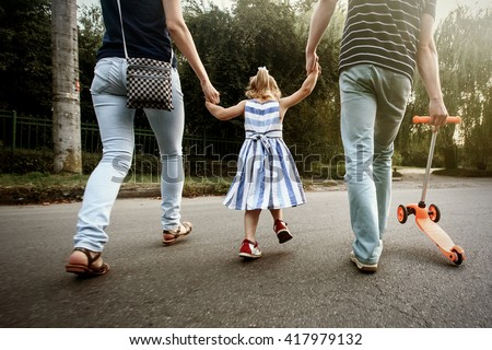 happy stylish parents holding hands with daughter and walking in sunny  street, amazing family moment - stock photo