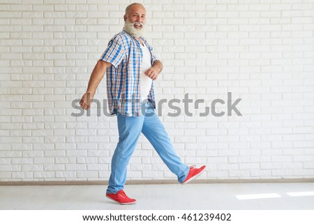 Happy stylish senior dressed in checkered shirt and jeans is walking in light white room, white brick wall and floor in background