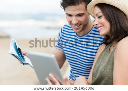 Happy stylish young couple on summer vacation at the beach looking up directions on a tablet computer smiling as they compare a map held by the husband as they plan their sightseeing - stock photo