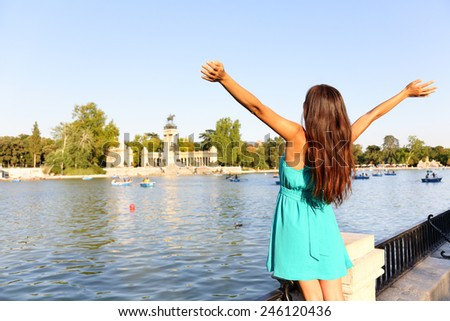 Happy success woman in Madrid park El Retiro. Successful girl cheerful with arms up outstretched in by lake Parque el Retiro in Madrid, Spain, Europe. Woman in summer dress. - stock photo