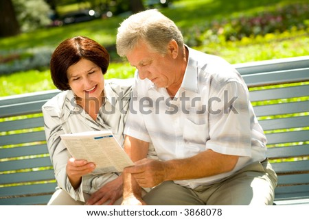 Happy successful attractive elderly couple reading together outdoors - stock photo