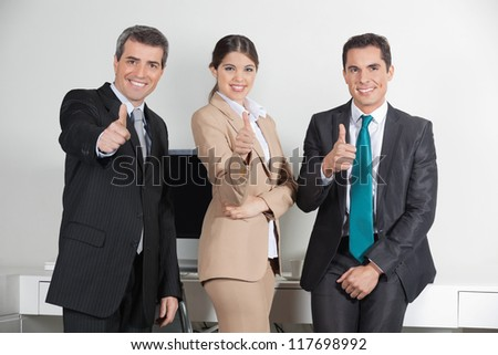 Happy successful business team in the office holding their thumbs up - stock photo