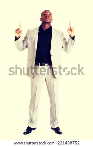 Happy successful businessman pointing on copy space. - stock photo