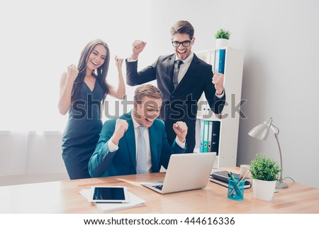 Happy successful businesspeople triumphing with raised hands and looking at laptop - stock photo