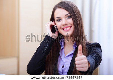 Happy successful businesswoman with cell phone and thumbs up gesture - stock photo