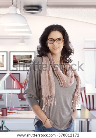 Happy successful casual caucasian businesswoman at home business office, standing, hand in pocket, wearing glasses, smiling, looking at camera.