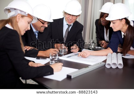 Happy successful engineers brainstorming on a new project with the blueprints - stock photo