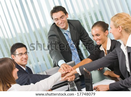 Happy successful gesturing business team at office
