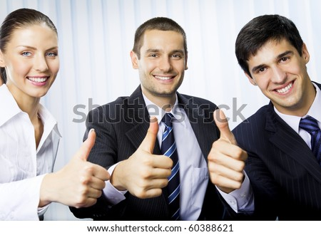 Happy successful gesturing businesspeople at office - stock photo