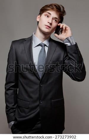 Happy successful young business man talking on cell phone - stock photo