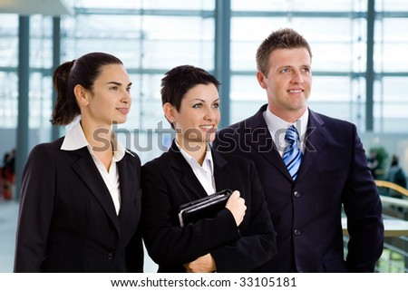 Happy successful young business people standing side by side at office lobby, smiling, looking away.