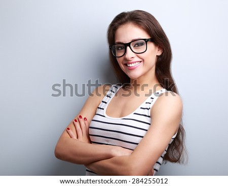 Happy successful young woman in glasses looking on blue background with empty copy space - stock photo