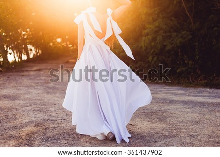 Happy summer Caucasian woman in white long dress and sandals with copy space,opposite the sunset,wedding tips,accessory summer style woman,gorgeous dress, motion shot,fashion outdoor photo,blond hair  - stock photo