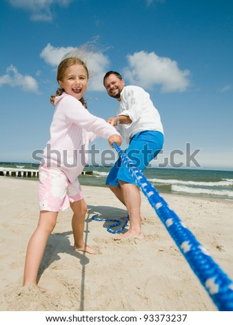 Happy summer holiday - family playing on the beach