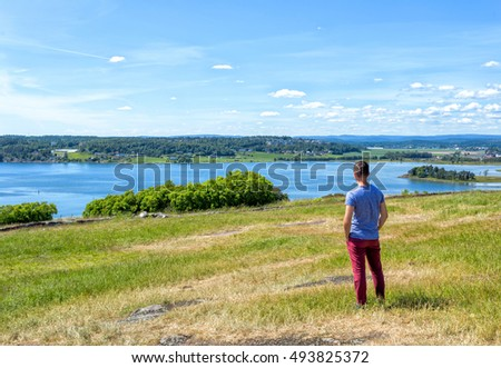 Happy summer vacation for young man on green meadow near sea
