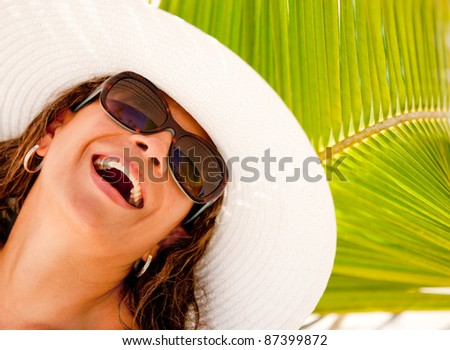 Happy summery woman wearing a hat and sunglasses - stock photo