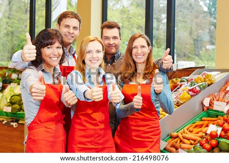 Happy supermarket staff team holding thumbs up in teamwork effort - stock photo