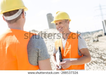 Happy supervisor discussing with colleague at construction site - stock photo