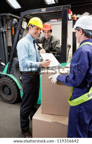 Happy supervisor showing clipboard to young foreman at warehouse - stock photo