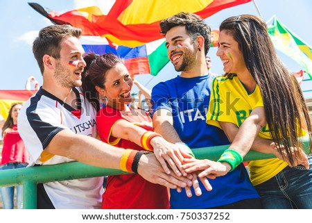 Happy supporters from different countries together at stadium. Fans from Italy, Germany, Spain, Brazil and other countries enjoying a match together. Sport, respect and fair play concepts