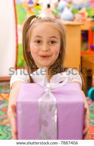Happy surpised girl showing the birthday present - stock photo