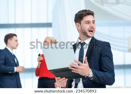 Happy surprise. Smiling businessman standing on a ladder and holding a laptop in his hands while his colleague businessmen talking in the background - stock photo