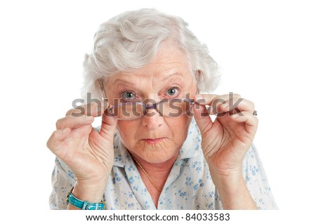 Happy surprised old senior lady looking through her eyeglasses isolated on white background - stock photo