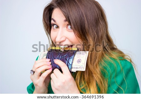 Happy surprised smiling businesswoman wearing in green jacket biting a big wallet and  money. Closeup portrait super happy excited successful young business woman holding money dollar bills