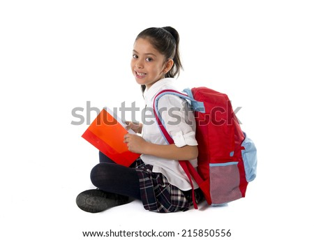 Happy sweet little latin child reading book smiling sitting on the floor with backpack in children education and back to school concept isolated on white background