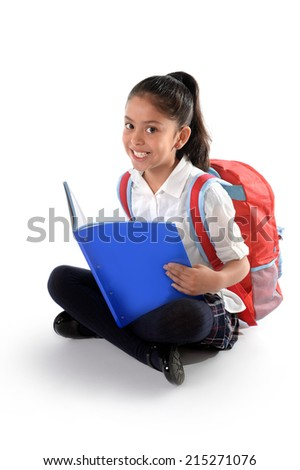 Happy sweet little latin child reading textbook or notepad smiling sitting on the floor with backpack in children education and back to school concept isolated on white background - stock photo
