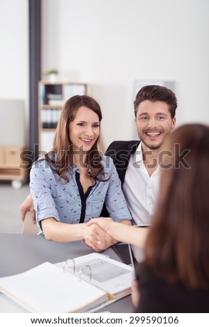 Happy Sweet Young Couple Handshaking a Real Estate Agent After Signing a Contract Inside the Office - stock photo