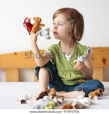 Happy sweet young girl playing with small puppets on the bed - stock photo