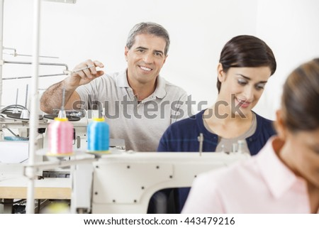 Happy Tailor Sitting With Colleagues Working In Sewing Factory - stock photo
